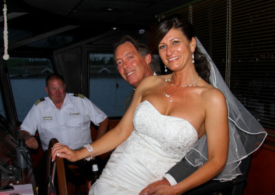 Blushing bride with groom in wheel house...